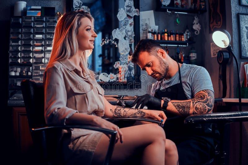 Tattoo master is creating new tattoo for customer stock photo
