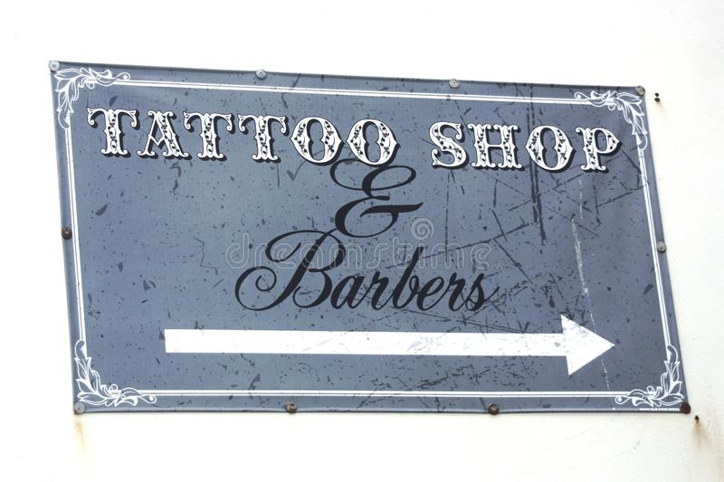Tattoo Shop & Barbers sign on a white wall. A Tattoo Shop & Barbers sign nailed to a white wall stock images