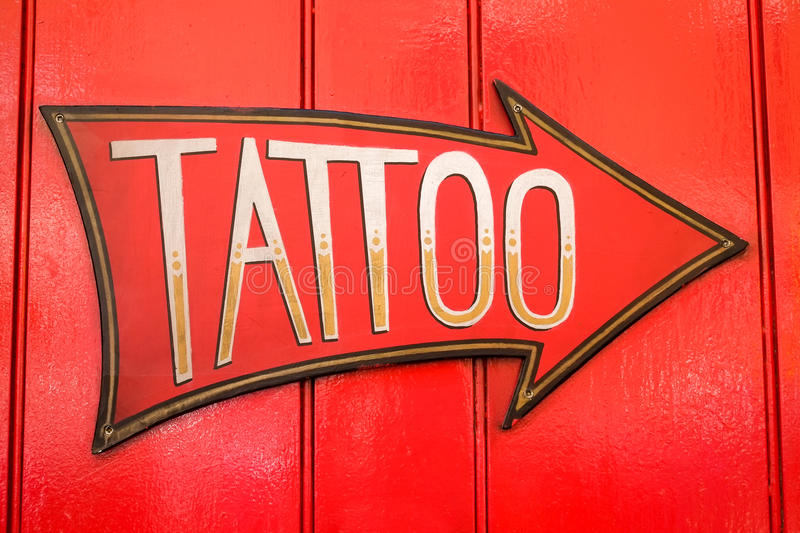 Tattoo sign with large arrow. Tattoo sign and arrow on a red door. London stock images