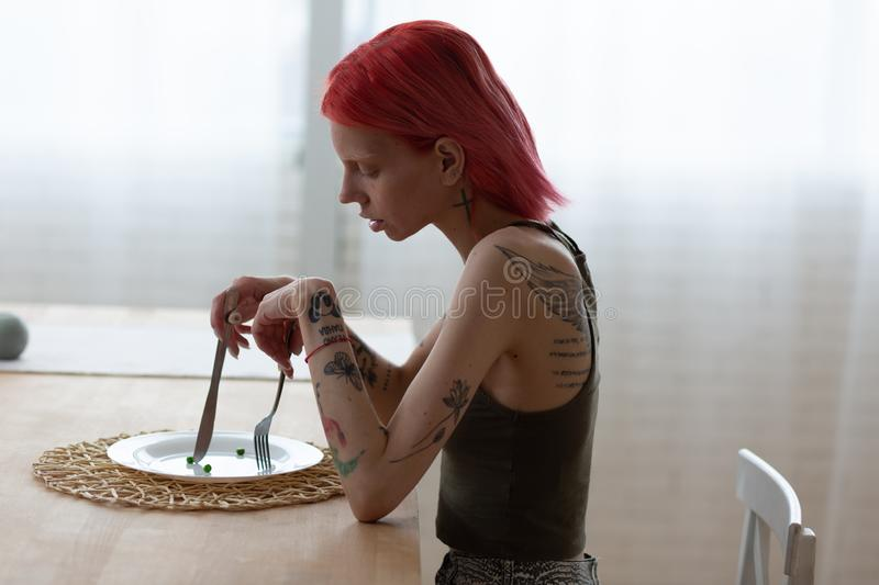 Anorexic woman with tattooed back sitting in front of empty plate. Tattooed back. Anorexic woman with tattooed back and arms sitting in front of empty plate in royalty free stock photography