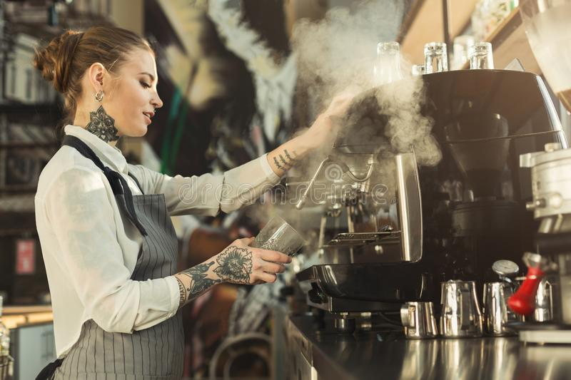 Tattooed barista making coffee in professional coffee machine stock images