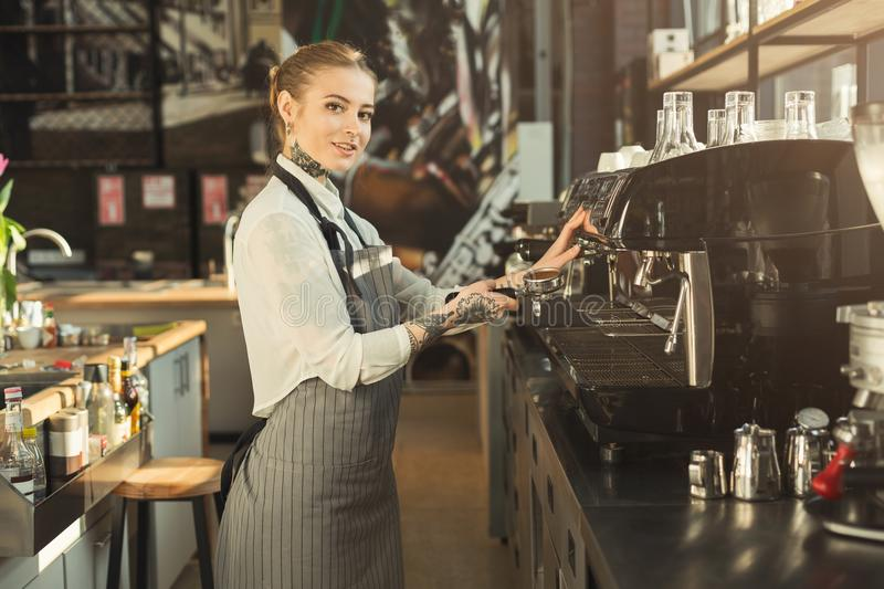 Tattooed barista making coffee in professional coffee machine royalty free stock photos