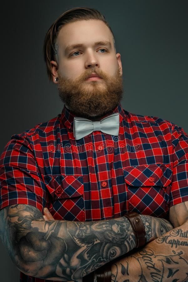 Tattooed bearded unformal male in red shirt and grey bow tie. stock images