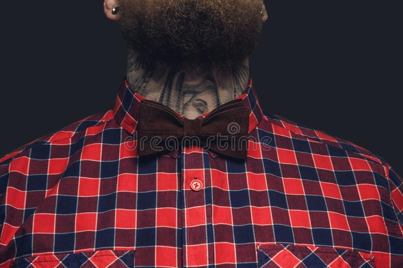 Tattooed bearded unformal male in red shirt and grey bow tie. royalty free stock image