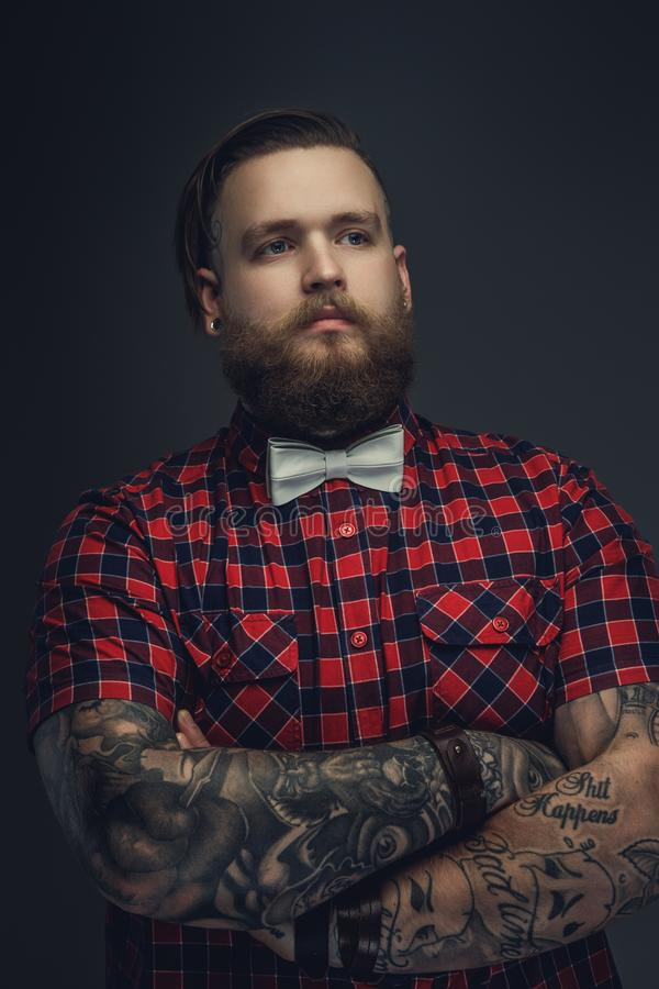 Tattooed bearded unformal male in red shirt and grey bow tie. royalty free stock photography