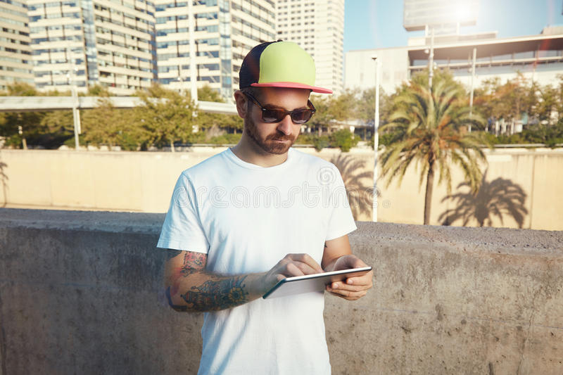 Tattooed bearded young man with a tablet in city royalty free stock photos