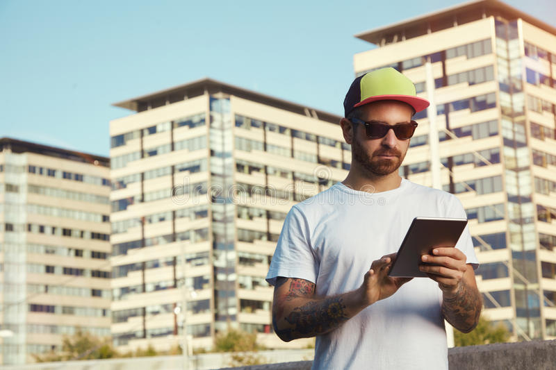 Tattooed bearded young man with a tablet in city royalty free stock image