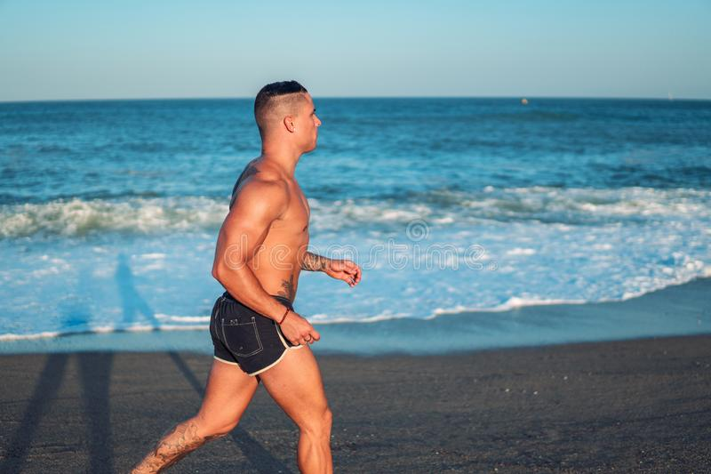 Tattooed bodybuilder sexy male coach at the beach. royalty free stock photo