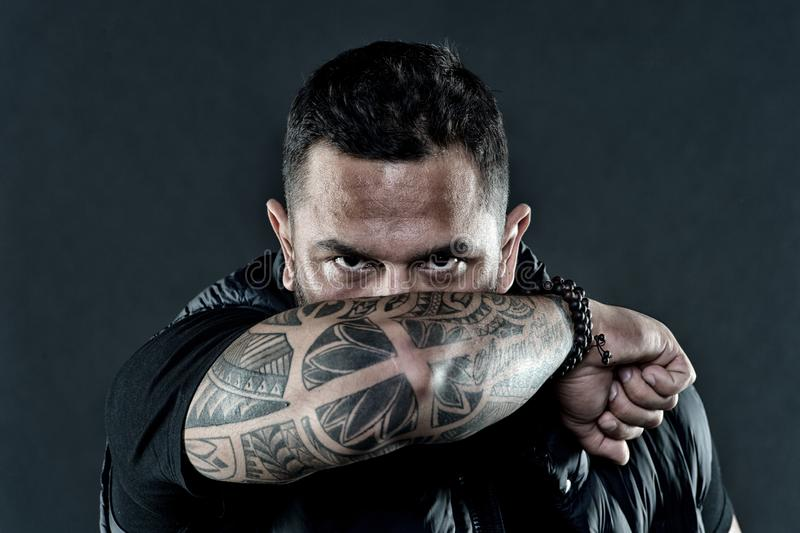 Tattooed elbow hide male face dark background. Visual culture concept. Tattoo can function as sign of commitment. Do stock photography