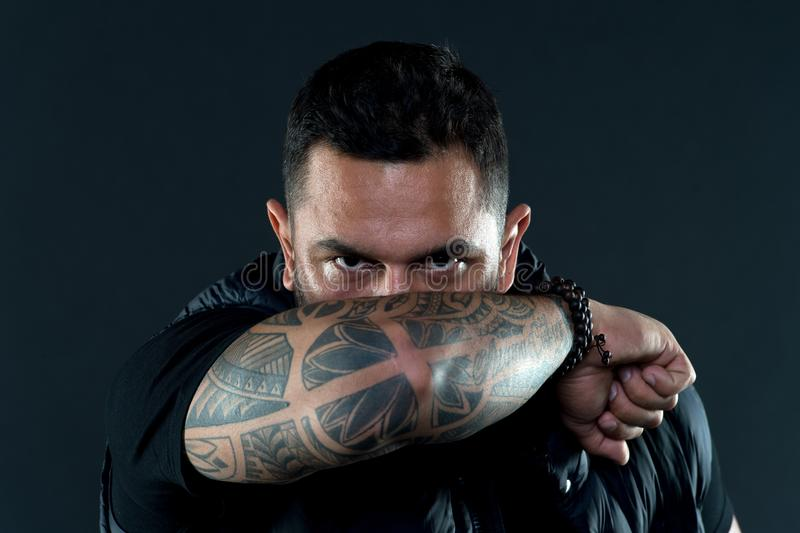 Tattooed elbow hide male face. Tattoo culture concept. Man brutal unshaven hispanic appearance tattooed arm. Bearded man. Posing with tattoos. Brutal macho with stock photos