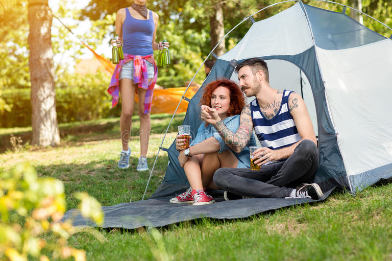 Tattooed guy and lassie sits and drinks beer in front of tent. At summer camp in nature royalty free stock photo