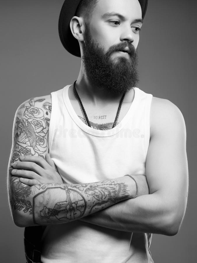 Man in hat. boy with tattoo. Black and white portrait. Tattooed handsome Man in Hat. Brutal hipster boy with tattoo. Black and white portrait royalty free stock image