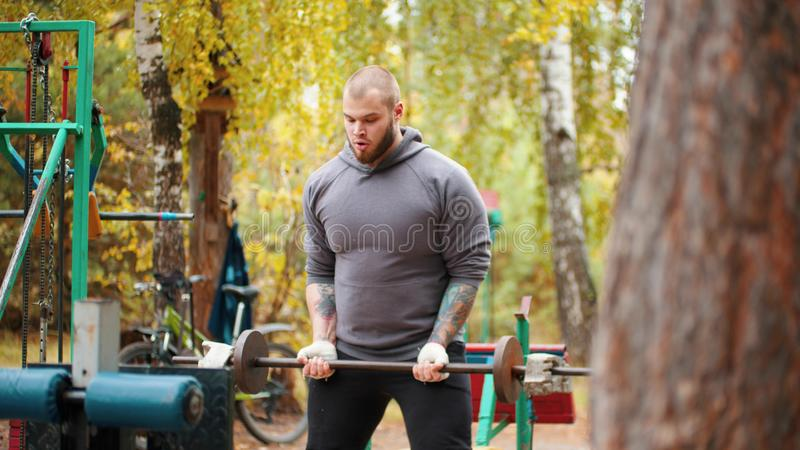 A tattooed man bodybuilder pumping his hands with the dumbbell behind his back - training on the outdoors sports ground royalty free stock photography
