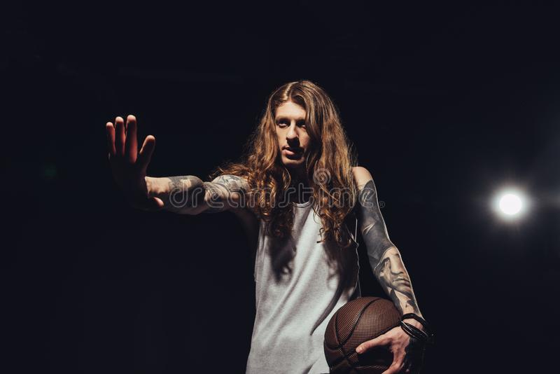 Tattooed man with long hair gesturing and holding basketball ball. Isolated on black with backlit royalty free stock image