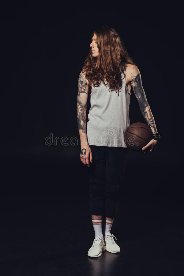 Tattooed man with long hair holding basketball ball. On black stock images