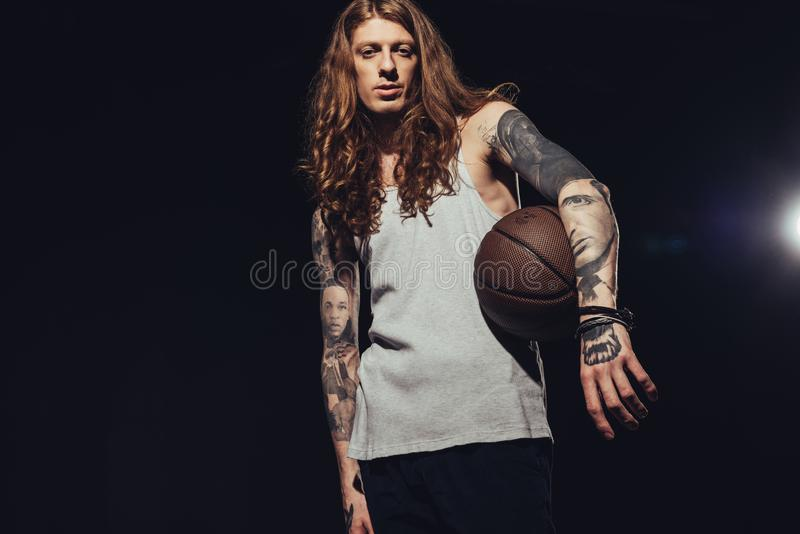 Tattooed man posing with basketball ball. Isolated on black with back light royalty free stock images