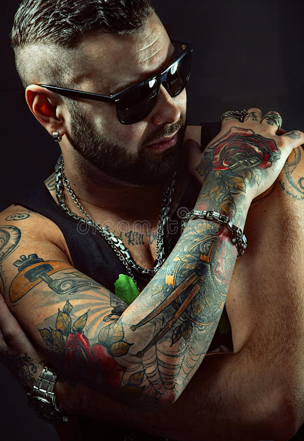 Tattooed man in sunglasses stock images