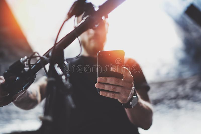 Tattooed muscular male holding mobile phone in hands and using map app for preparing ride road route. Discover urban royalty free stock images