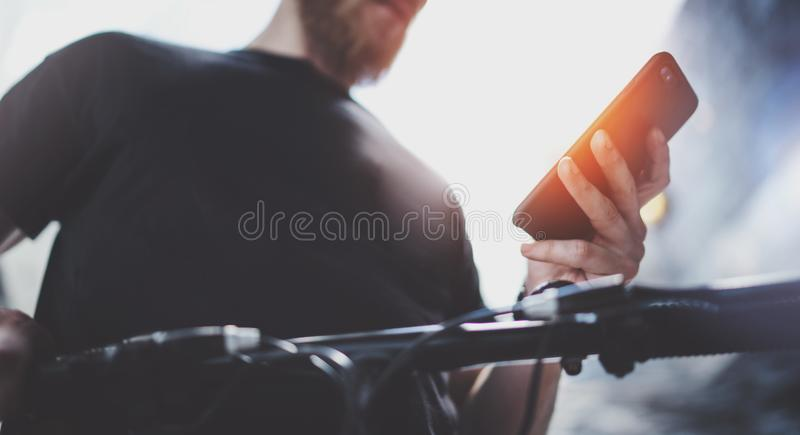 Tattooed muscular male holding mobile phone in hands and using map app for preparing ride road route. Discover urban stock photo