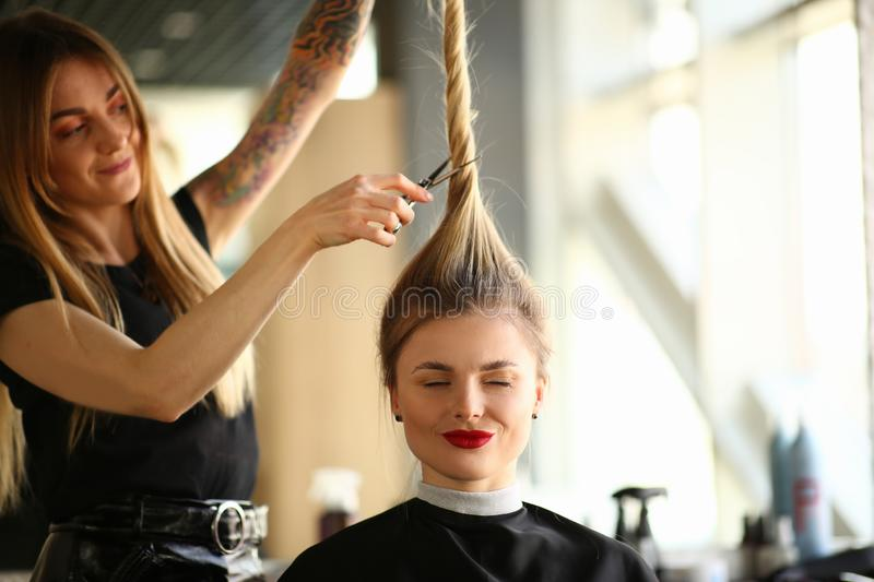 Tattooed Stylist Cutting Hair of Closed Eyes Woman. Hairdresser Using Scissors for Making Hairstyle for Female Client. Blonde Girl Getting Haircut in Beauty royalty free stock photo