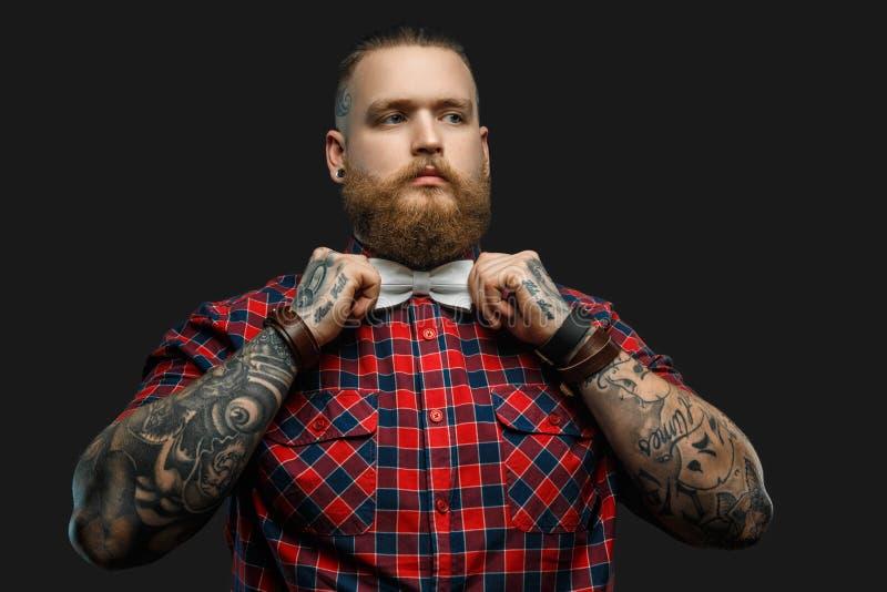 Tattooed uppsökte den unformal mannen i röd skjorta och grå färgfluga arkivbilder