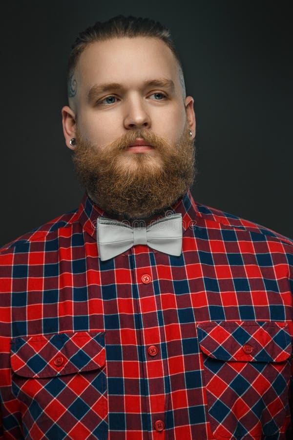 Tattooed uppsökte den unformal mannen i röd skjorta och grå färgfluga royaltyfri fotografi