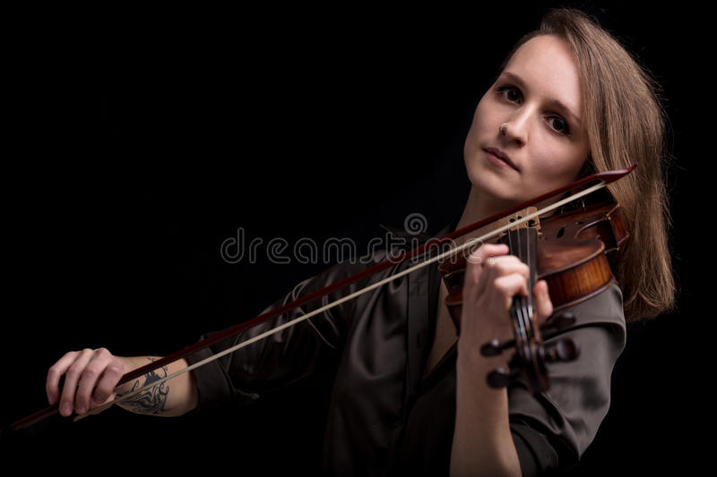 Tattooed violinist woman playing in black background. Young beautiful woman violinist player looking at camera over instrument on her shoulder holding bow stock photos