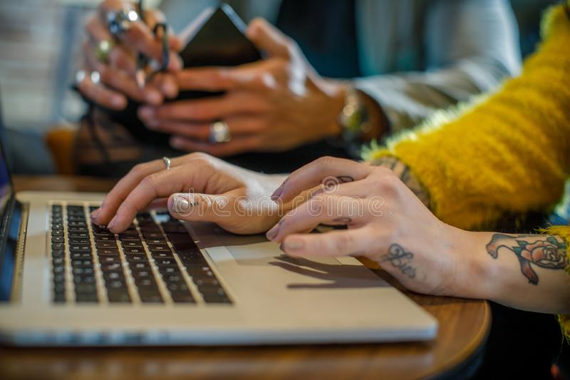 Tattooed woman hands writing and using laptop, man in background.Group of multiethnic people having business team royalty free stock photos