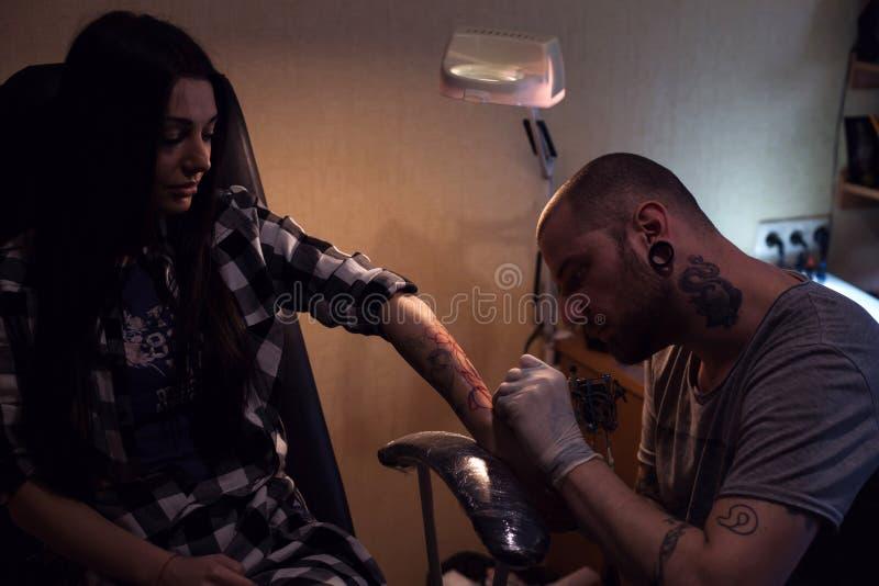 Tattooer robi tatuażowi dla kobiety zdjęcie royalty free