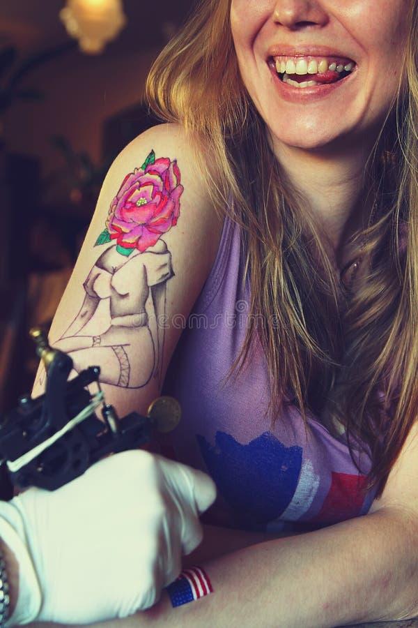 Tattooer visningprocess av att göra en tatuering på ung härlig hipsterkvinna fotografering för bildbyråer