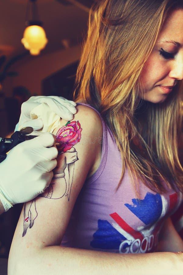 Tattooer visningprocess av att göra en tatuering på ung härlig hipsterkvinna arkivfoton