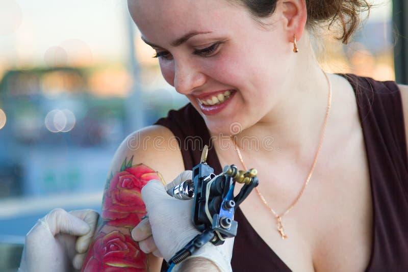 Tattooer visningprocess av att göra en tatuering på ung härlig hipsterkvinna med den röda armen för lockigt hår Tatueringdesign i arkivfoton