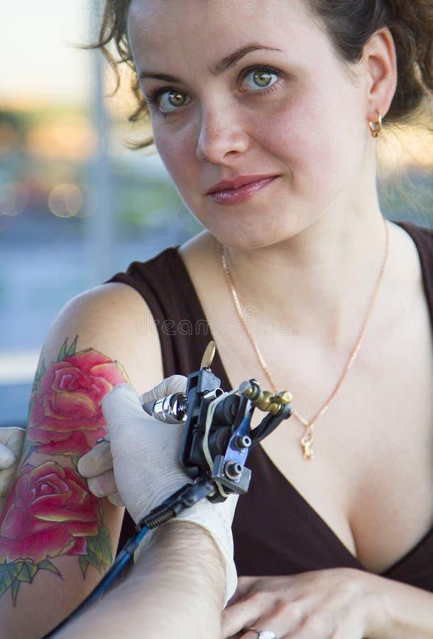 Tattooer visningprocess av att göra en tatuering på ung härlig hipsterkvinna med den röda armen för lockigt hår Tatueringdesign i arkivfoto