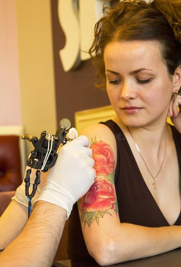Tattooer visningprocess av att göra en tatuering på ung härlig hipsterkvinna med den röda armen för lockigt hår Tatueringdesign i arkivbilder