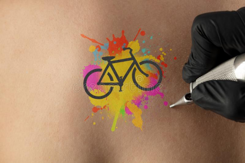 Tattooing bicycle concept on naked back. Hand tattooing colourful bicycle concept on naked clear skin royalty free stock images