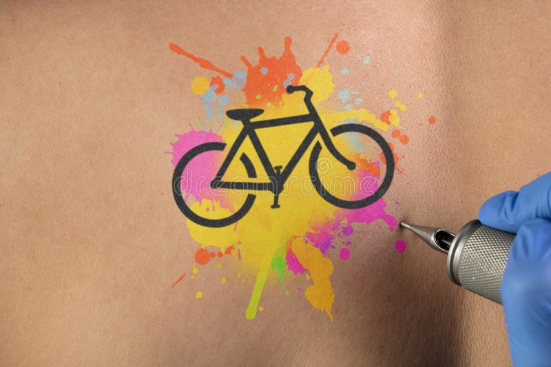 Tattooing bicycle concept on naked back. Hand tattooing colourful bicycle concept on naked clear skin royalty free stock photo