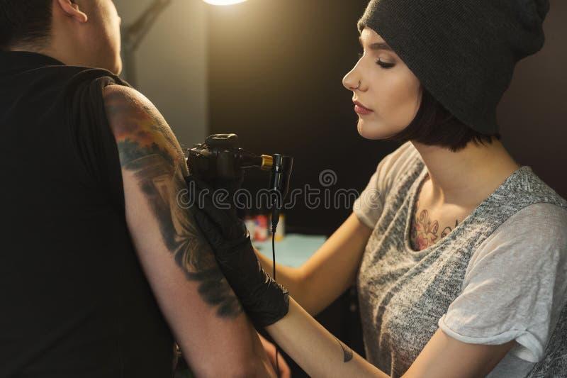 Tattooist de la mujer joven que hace el tatuaje en hombro fotografía de archivo libre de regalías
