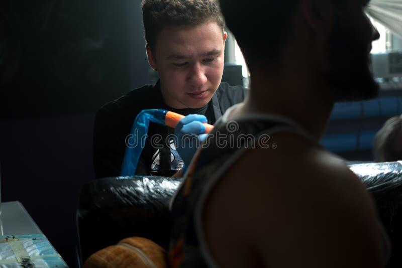 Tattooist in den sterilen Handschuhen, die jungen Mann tätowieren stockfoto