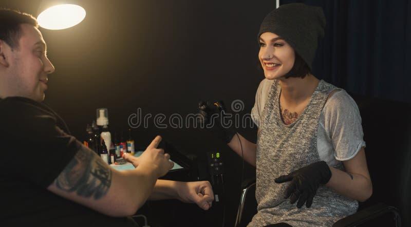 Tattooist för ung kvinna som gör tatueringen på den manliga armen arkivbild