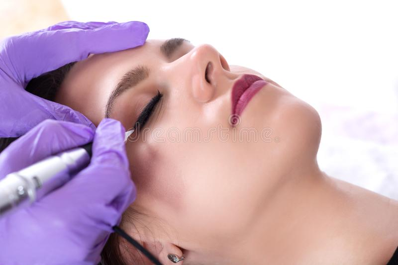 Tattooist making eyeliner with permanent make up on beautiful young girl stock image