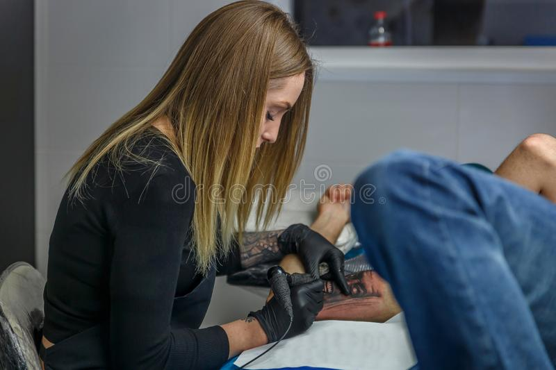 A tattooist woman is sketching a tattoo on the arm of  a boy, in her narrow studio. A tattooist women is sketching a tattoo on the arm of a boy in her little and royalty free stock image