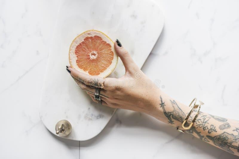 Tatuaż kobiety ręka Dostaje pomarańcze z Marmurowym tłem fotografia royalty free
