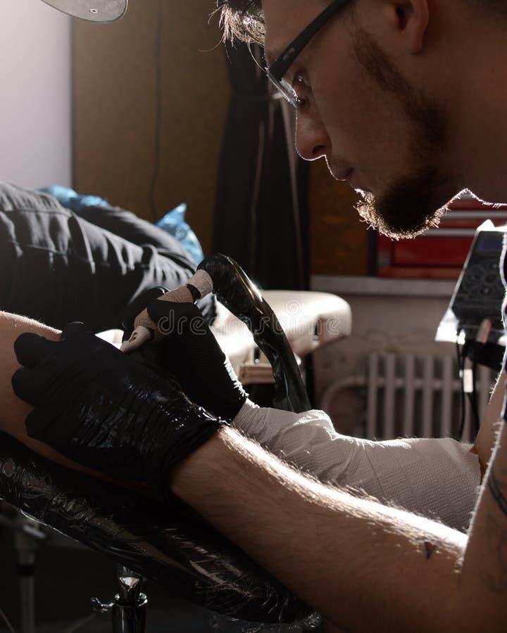 Tatuażu artysta robi tatuażowi na jego ręka mężczyzna zbliżenie zdjęcia royalty free