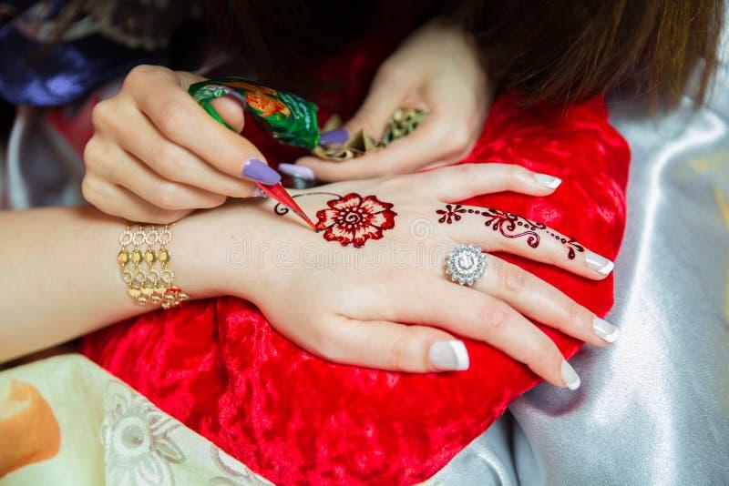 Tatuaje del diseño de la alheña Mujeres que aplican el tatuaje de la alheña de las rosas en las manos de las mujeres La mujer dib imagen de archivo libre de regalías
