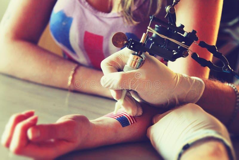 Tatuatore che mostra processo di fabbricazione del tatuaggio sulla giovane bella donna dei pantaloni a vita bassa fotografia stock libera da diritti