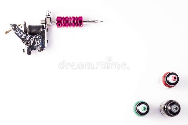 Tatuera maskinen och tre flaskor av färgpulver som isoleras på vit bakgrund arkivfoto