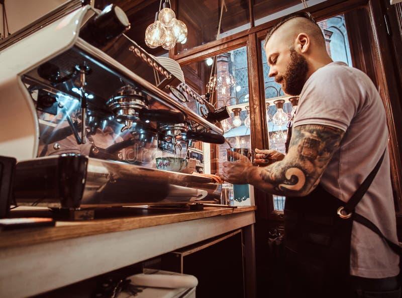 Tatuerad barista med stilfullt skägg- och frisyrarbete på en kaffemaskin i en coffee shop eller en restaurang royaltyfri bild