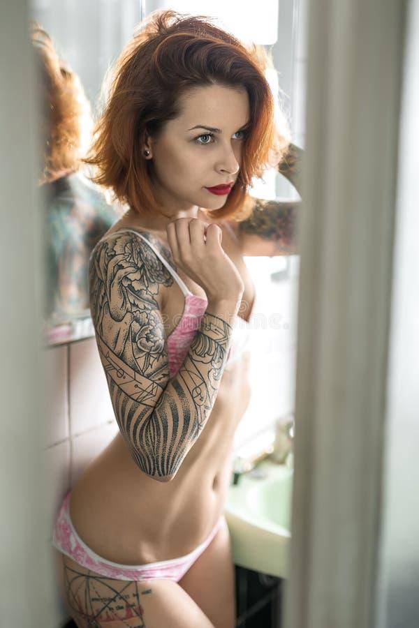Tatuerad flicka i badrum royaltyfri fotografi