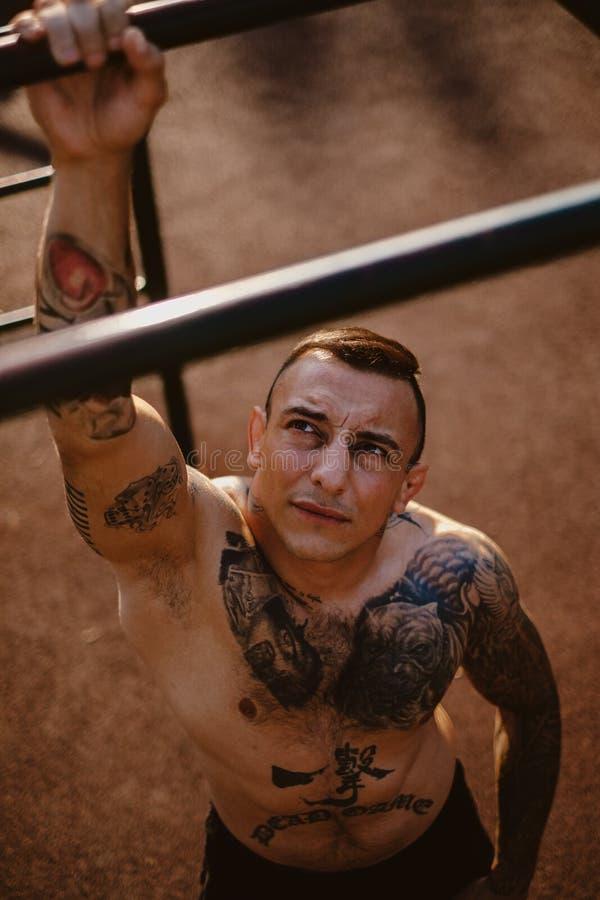 Tatuerad kämpe som hänger från den utomhus- idrottshallstången royaltyfri bild
