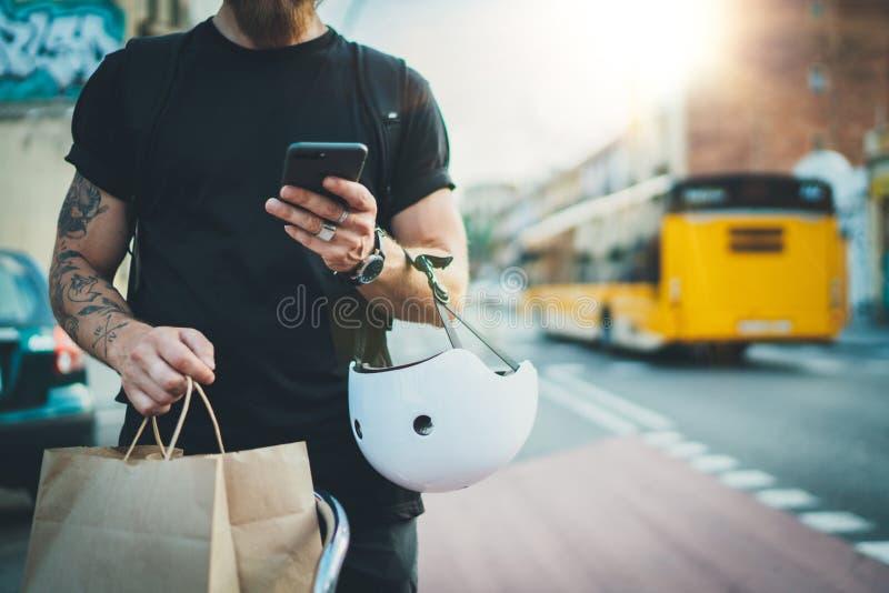 Tatuerad mankurir som använder en översiktsapp på mobiltelefonen för att finna leveransadressen i staden Kurircykelleverans arkivfoto